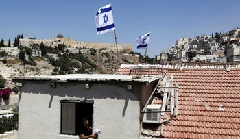 File photo: A man is seen from a window as Israeli flags fly on top of a house in Silwan neighborhood of east Jerusalem, August 27, 2015.
