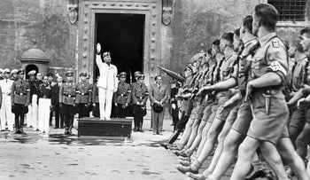Italian dictator Benito Mussolini performing a fascist salute as he welcomes German Nazi Youth, Rome, October 1936.