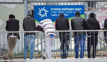 File photo: People wait in front of the entrance he Population, Immigration and Border Authority office in Bnei Brak, April 2018.