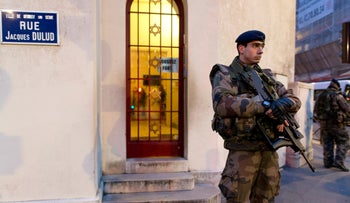 French soldiers patrol in front of a synagogue outside Paris as part of France's national security alert system, January 21, 2015