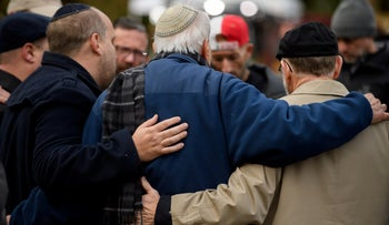 People pray together in front of at a memorial for victims of the mass shooting that killed 11 people and wounded 6 at the Tree Of Life Synagogue on October 29, 2018