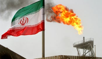 A gas flare on an oil production platform in the Soroush oil fields is seen alongside an Iranian flag in the Persian Gulf, July 25, 2005.