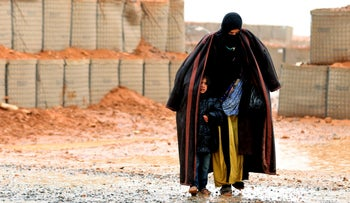 A Syrian refugee from the informal Rukban camp walks in the rain as she shelters a young child outside a UN-operated medical clinic immediately on the Jordanian side, March 1, 2017.