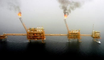 Gas flares from an oil production platform at the Soroush oil fields in the Persian Gulf, south of the capital Tehran, July 25, 2005.