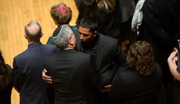 Wasi Mohamed from the Islamic Center of Pittsburgh is hugged by a rabbi during a service to honor the victims of Saturday's mass shooting at the Tree Of Life synagogue, October 28, 2018.