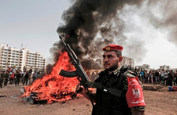 Members of the Palestinian Hamas movement security stand guard as others burn a pile of confiscated drugs in Gaza City on October 22, 2018