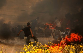 Palestinian protesters burn tyres during a demonstration on the beach near the maritime border with Israel, in the northern Gaza Strip, on October 22, 2018