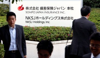 Pedestrians walk past a sign for NKSJ Holdings Inc.'s Sompo Japan Insurance Inc. outside the company's headquarters, in Tokyo, Japan, on Friday, June 18, 2010