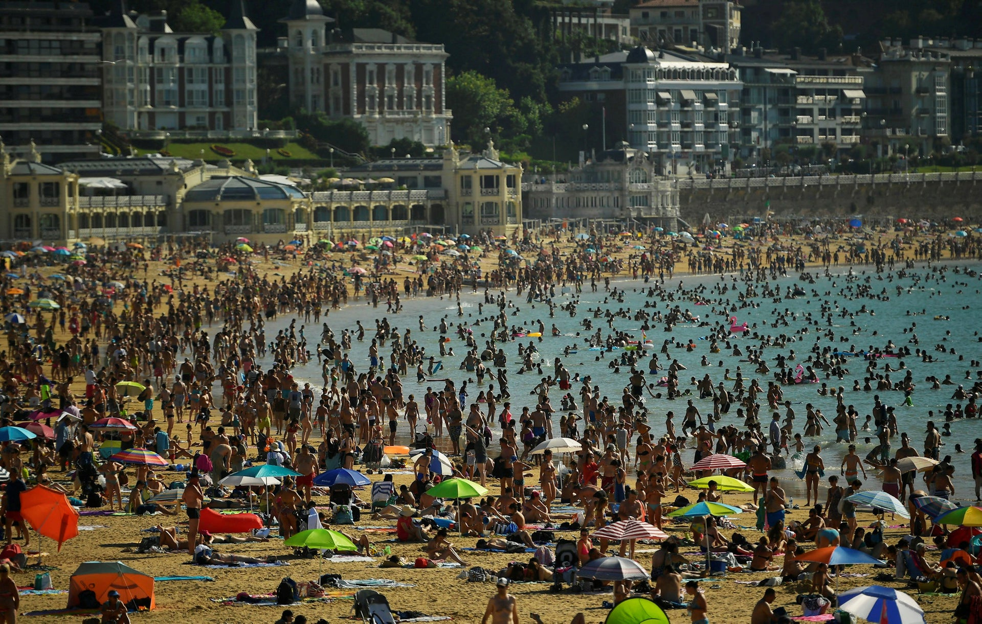 People crowd La Concha beach in the Basque city of San Sebastian, northern Spain, Friday, Aug. 3, 2018. Hot air from Africa is bringing a heat wave to Europe, prompting health warnings about Sahara Desert dust and exceptionally high temperatures that could peak at 47 degrees Celsius (117 Fahrenheit) in Spain and Portugal.