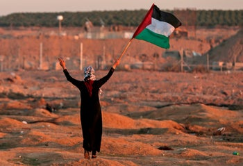 A demonstrator holding the Palestinian flag along the Gaza border, November 2, 2018.