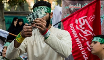 A protester prepares to set fire to a $100 bill during a demonstration on the anniversary of the U.S. embassy seizure, Tehran, Iran, November 4, 2018.
