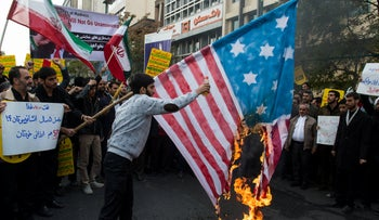 A protester sets fire to the American flag during a demonstration on the anniversary of the U.S. embassy seizure, in Tehran, Iran, November 4, 2018.