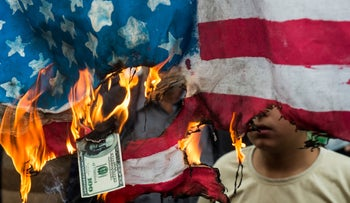 Protesters burn an American flag and a U.S. one-hundred dollar bill during a demonstration on the anniversary of the U.S. embassy seizure, in Tehran, Iran, on Sunday, Nov. 4, 2018.