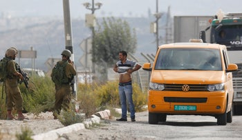 Israeli soldiers check a Palestinian after a stabbing attack at Huwara checkpoint near the West Bank city of Nablus, Thursday, Oct. 11, 2018