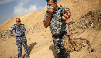 A member of the Iraqi forces holds a skull they dug up from a mass grave discovered in the Hamam al-Alil area after they recaptured the area from Islamic State (IS) group jihadists, Nov. 08, 2016.
