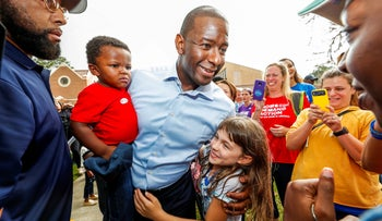 Democratic gubernatorial candidate Andrew Gillum holds his son Davis as he greets well-wishers outside his polling place, Tallahassee, Florida, November 6, 2018.