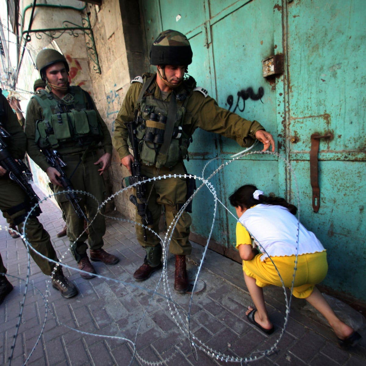 Israeli soldiers let a Palestinian girl make her way past a barbed wire barricade set up to prevent protesting Palestinians from accessing an Israeli settlement, in Hebron, Sept. 14, 2011.