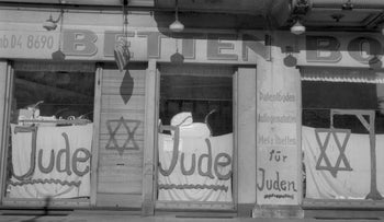 A Jewish-run shop bearing antisemitic Nazi graffiti, leading up to the 1938 antisemitic campaign known as Kristallnacht, in Berlin.