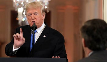 U.S. President Donald Trump speaks as CNN's Jim Acosta, standing at right, listens, during a news conference in the East Room of the White House, November 7, 2018, in Washington.