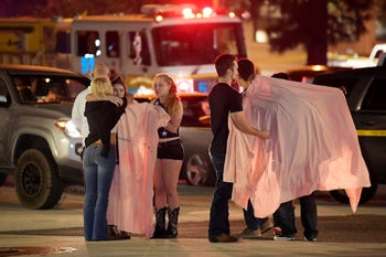 """People comfort each other as they stand near the scene Thursday, Nov. 8, 2018, in Thousand Oaks, Calif. where a gunman opened fire Wednesday inside a country dance bar crowded with hundreds of people on """"college night,"""" wounding 11 people including a deputy who rushed to the scene. Ventura County sheriff's spokesman says gunman is dead inside the bar."""