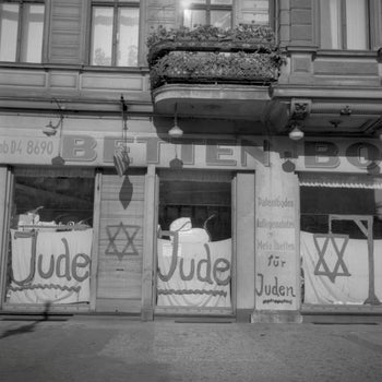 """A Jewish-run shop in Berlin bearing anti-Semitic graffiti, June 1938; Kristallnacht occurred five months later. Germans now prefer to use the term """"November pogrom"""" to describe the atrocity."""
