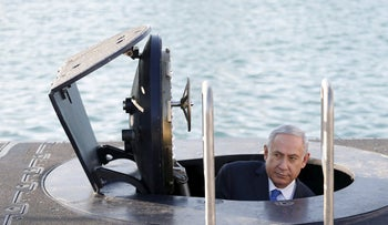 Benjamin Netanyahu climbs out after a visit inside the Rahav, the fifth submarine in the fleet, after it arrived in Haifa port January 12, 2016