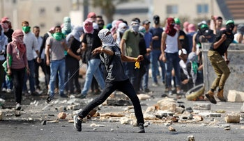 A Palestinian protester from Birzeit University throws stones during clashes with Israeli troops near the Jewish settlement of Beit El, near the West Bank city of Ramallah, on October 2, 2018.