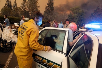 Hospital workers and first responders evacuate patients from the Feather River Hospital as the Camp Fire moves through the area in Paradise, California, November 8, 2018.