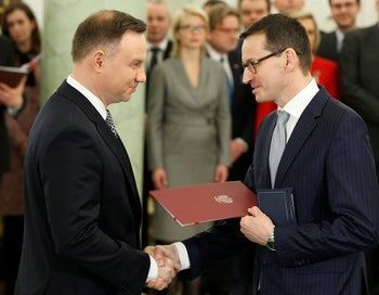 Polish President Andrzej Duda hands new Prime Minister Mateusz Morawiecki the document of his appointment as head of government in Warsaw, 2017.