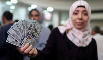A Palestinian Hamas-hired employee displays U.S. dollar notes after receiving her salary, in the southern Gaza Strip, November 9, 2018.