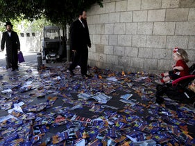Ultra-Orthodox men walk on a street covered with campaign flyers in the Mea Shearim neighborhood of Jerusalem on October 30.