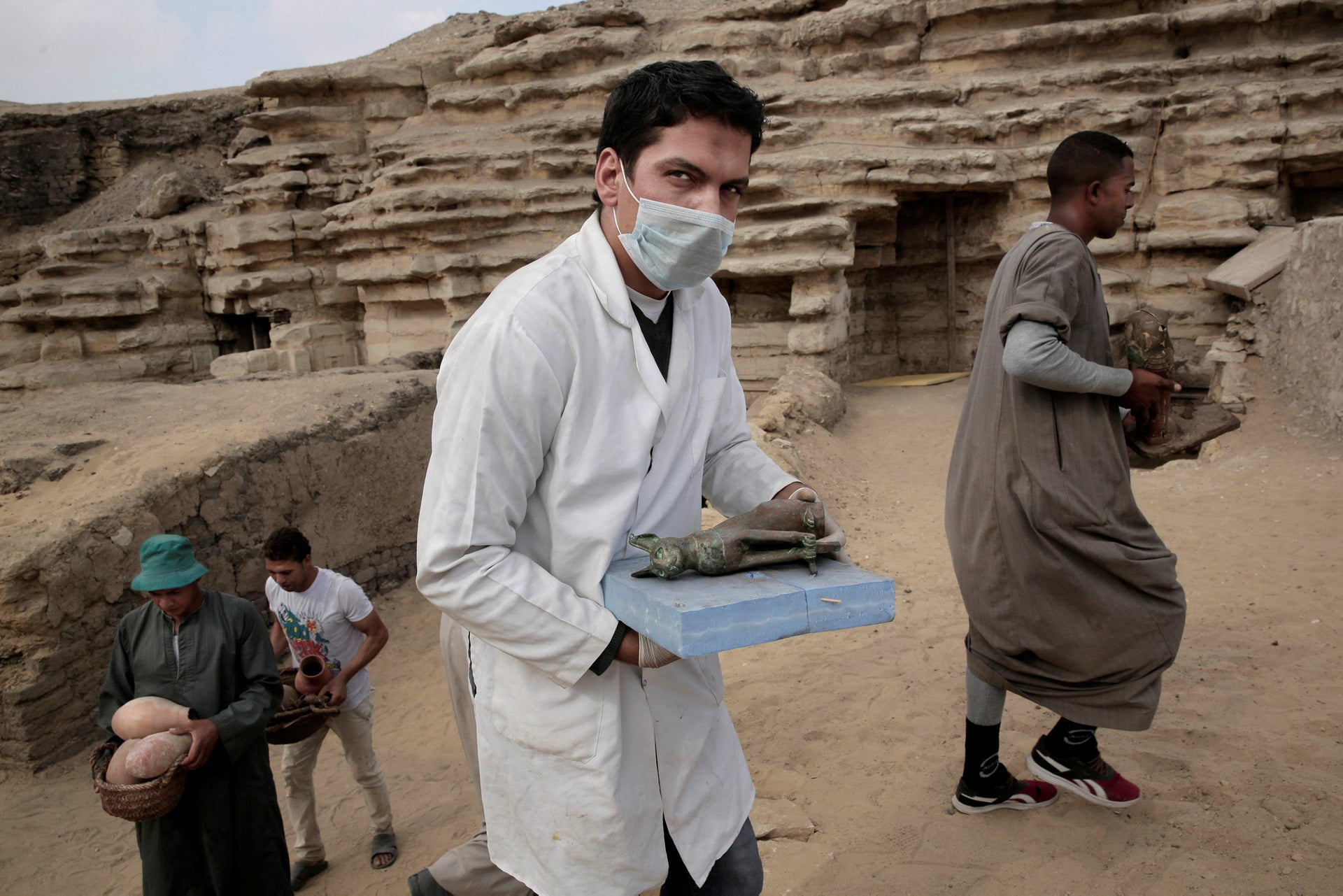 An archeologist and workers from Upper Egypt carry artifacts found in newly discovered tomb, at an ancient necropolis near Egypt's famed pyramids in Saqqara, Giza, Egypt, Saturday, Nov. 10, 2018. A top Egyptian antiquities official says local archaeologists have discovered seven Pharaonic Age tombs near the capital Cairo containing dozens of cat mummies along with wooden statues depicting other animals.