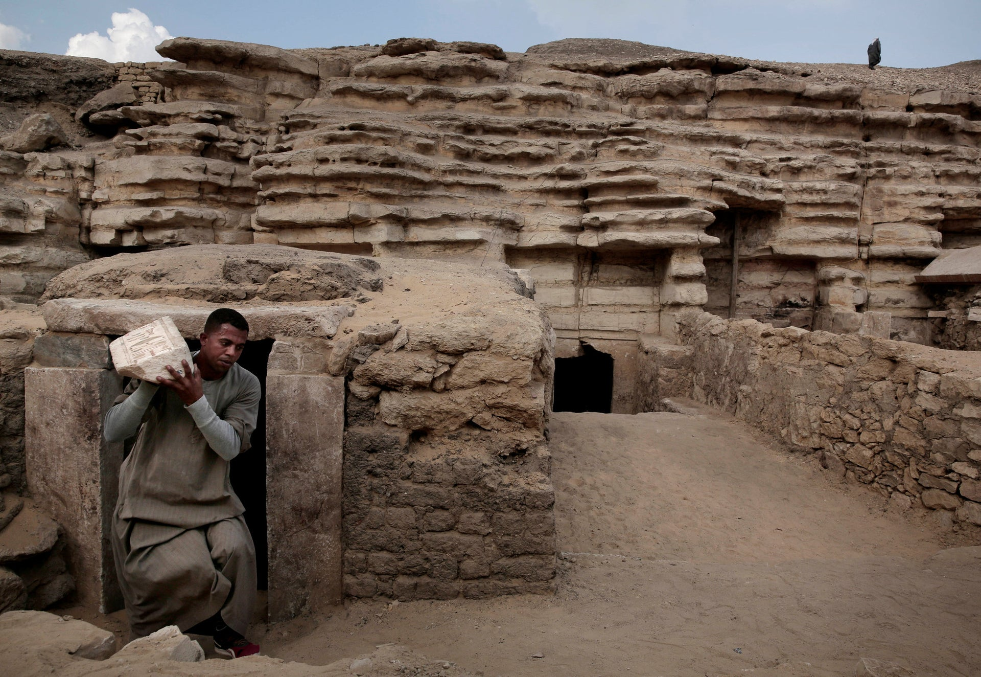 A worker carries an artifact out of a tomb, at an ancient necropolis near Egypt's famed pyramids in Saqqara, Giza, Egypt, Saturday, Nov. 10, 2018. A top Egyptian antiquities official says local archaeologists have discovered seven Pharaonic Age tombs near the capital Cairo containing dozens of cat mummies along with wooden statues depicting other animals.