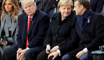 U.S. President Donald Trump, second left, watches French President Emmanuel Macron putting his hand on German Chancellor Angela Merkel's knee during ceremonies at the Arc de Triomphe Sunday, Nov. 11, 2018 in Paris