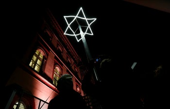 People taking pictures of a light symbol, marking the place where Viennese synagogues once stood before they were destroyed, after a ceremony to mark the 80th anniversary of Kristallnacht, in Vienna, Austria, November 8, 2018.