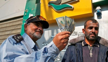 A Palestinian man shows his money after receiving his salary in the southern Gaza Strip November 9, 2018.