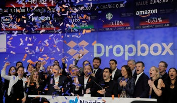 Dropbox Inc. co-founders Drew Houston and Arash Ferdowsi celebrate while ringing the opening bell on the Nasdaq Stock Market as Dropbox is listed for the company's IPO, March 23, 2018.