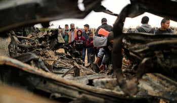 Palestinians gather around the remains of a vehicle that was destroyed in an Israeli air strike, in Khan Younis in the southern Gaza Strip November 12, 2018.
