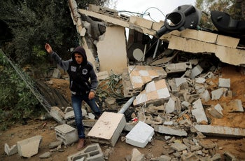 A Palestinian walks through the debris of a building destroyed in an Israeli air strike, in Khan Younis in the southern Gaza Strip November 12, 2018.