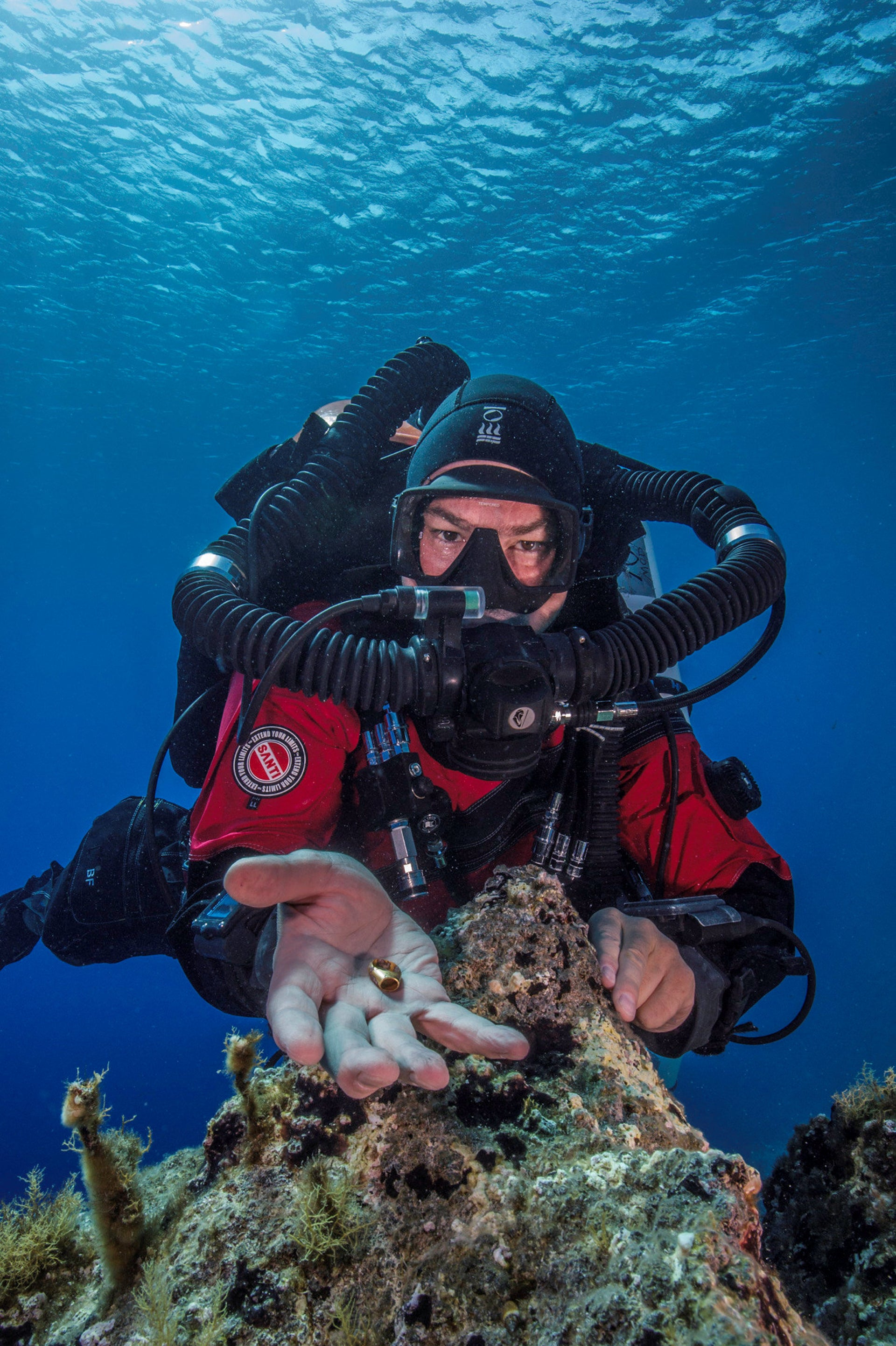 Foley lifting a gold ring found on the bottom of the sea