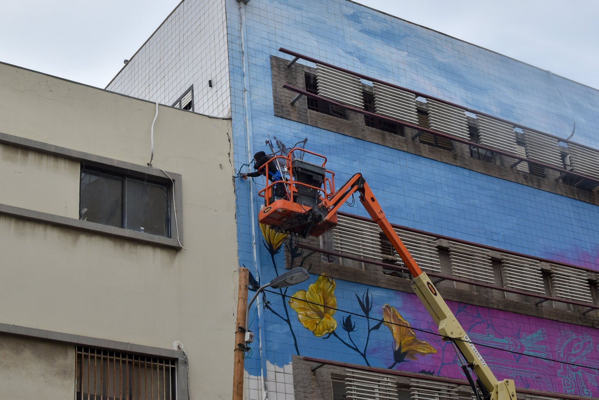 Libre working on the old Honigman factory in south Tel Aviv. The work includes a wolf, a lamb and a character inspired by a janitor at a nearby school.