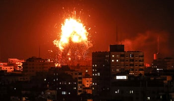 A ball of fire is seen above the building housing the Hamas-run TV station Al-Aqsa TV during an Israeli airstrike, Gaza city, November 12, 2018.