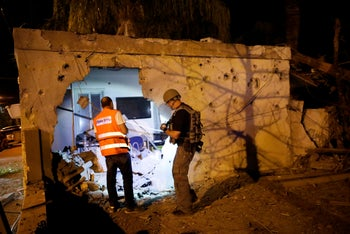 Security personnel and a municipality worker check a damaged house following a rocket attack from Gaza, Ashkelon, Israel, November 12, 2018.