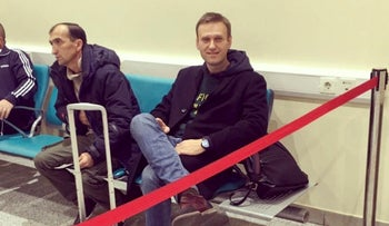 Photo released by Anti-corruption Foundation Press Service shows Russian anti-corruption crusader Alexei Navalny sitting at Domodedovo international airport outside Moscow, Russia, Nov. 13, 2018.