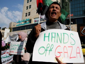 A Palestinian protester holding a sign that reads 'Hands off Gaza' during a demonstration in Hebron against Israeli airstrikes on Gaza, November 13, 2018.
