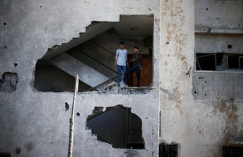 Palestinians look out of their house that was damaged in an Israeli air strike, in Gaza City November 13, 2018.