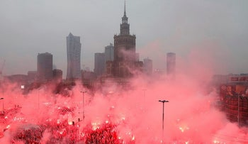 People carry Polish flags and flares as they sing Polish national anthem during a march marking the 100th anniversary of Polish independence in Warsaw, Poland November 11, 2018