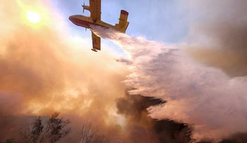 An air tanker drops water on a fire along the Ronald Reagan (118) Freeway in Simi Valley, Calif., Monday, Nov. 12, 2018.