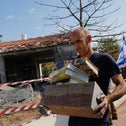 An Israeli man takes his belongings from a house damaged by a rocket fired from the Gaza Strip, in the southern Israeli city of Ashkelon, November 13, 2018.