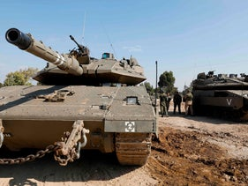 Israeli soldiers gather around Merkava tanks stationed along the Israeli border with the Gaza Strip, November 13, 2018.